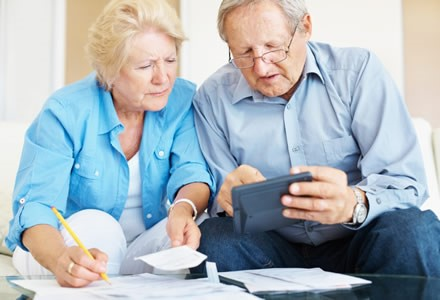 Two elderly people reviewing paperwork