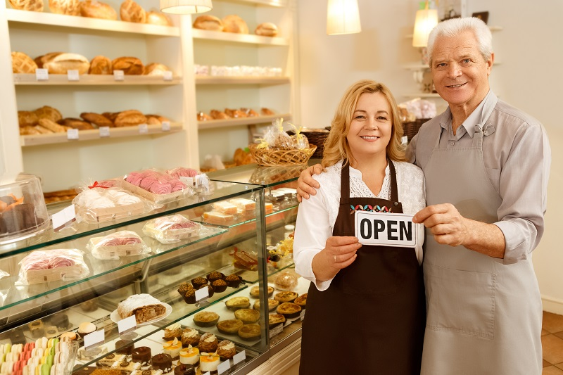 "Two people in a bakery, with an ""open"" sign"